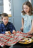 Two children cutting wrapping paper
