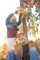 Girl throwing autumn leaves on brother