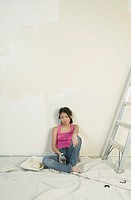 Asian woman resting while painting unfinished room