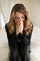 Woman sitting on bed crying