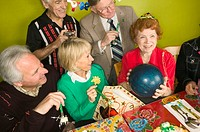 Senior woman holding bowling ball as birthday present