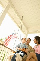 Hispanic military solder and family sitting on porch swing