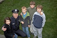 Male police officer smiling with children