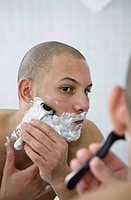 Young man shaving in front of bathroom mirror