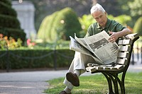 Senior man reading newspaper on park bench