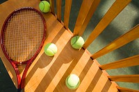 Tennis balls and racket on bench