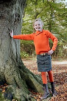 Young girl leaning against tree