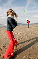 Father and daughter flying kite on beach