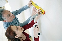 Couple putting nail in wall with level