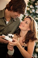 Couple exchanging Christmas gifts (thumbnail)