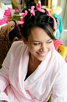Young woman wearing bathrobe with hair in rollers