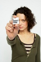 Young woman holding out a square of paper saying 'I Want You'