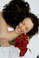 Young man embracing young woman with bouquet of roses (thumbnail)