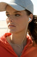 Young woman listening to earbuds, wearing baseball cap