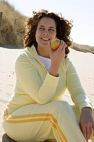 Woman eating apple at beach