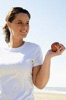 Woman eating apple at beach (thumbnail)