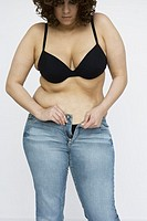 Woman in bra struggling with zipper on jeans