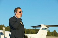 Businessman talking on his cell phone standing beside airplane
