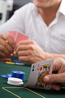 Close-up of cards on poker table, man in background