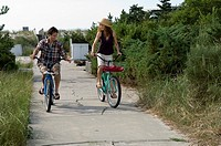 Adult couple riding bicycles on beach path