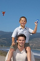 Son flying a kite from fatherÆs shoulders