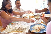 Family of Indian ethnicity eating take-out food