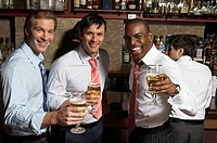 Three businessmen at bar with drinks