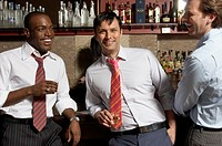 Three businessmen at bar talking