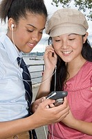 Two teenage girls with mp 3 player outdoors