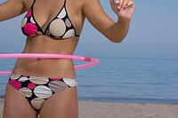 Mid section view of young woman playing with hula-hoop on beach