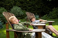 Young boys relaxing in backyard lawn chairs