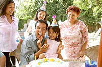 Young Hispanic girl putting icing on father´s face