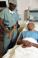 African male surgeon describing operation to patient