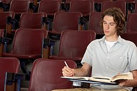 Student taking notes in auditorium