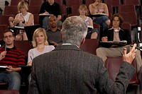 Older man teaching in auditorium full of young students