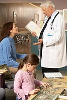 Doctor talking to mother while daughter is playing