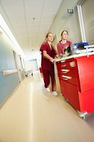 Nurses pushing medical equipment through corridor