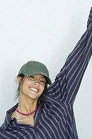 Teenage girl, one arm in the air, smiling at camera, portrait