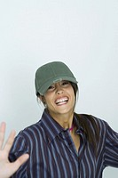 Teenage girl wearing cap, smiling, arms out, portrait