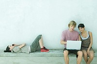 Group of young friends using laptop and cell phone