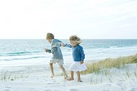 Sister and brother holding hands on beach