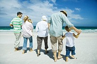 Three generation family walking on beach, rear view
