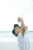 Boy drinking from water bottle on beach