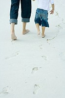 Father and son walking on sand, low section, rear view
