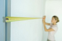 Woman measuring wall with measuring tape, focus on foreground