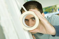 Man putting masking tape on surface, looking through hole