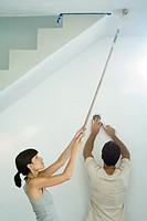Woman painting ceiling with paint roller while man changes lightbulb