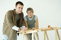 Couple leaning on sawhorses, using measuring tape, smiling at camera