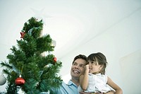 Father and daughter placing star on top of Christmas tree