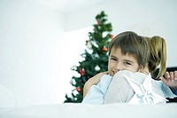 Mother hugging son, Christmas tree in background